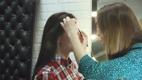 Artista de maquillaje de la mujer joven que hace a la muchacha morena hermosa del cambio de imagen en salón de belleza almacen de video