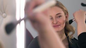 Artista de maquillaje de la mujer que hace a la muchacha rubia del maquillaje que usa cepillos Cierre para arriba metrajes