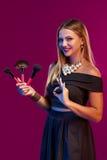 Artista de maquillaje de la mujer que se coloca con los cepillos fotos de archivo