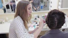 Artista de maquillaje del estilista que hace maquillaje y el pelo en un sal?n de belleza almacen de video