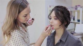 Artista de maquillaje del estilista que hace maquillaje y el pelo en un sal?n de belleza Maquillaje profesional metrajes