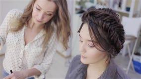 Artista de maquillaje del estilista que hace maquillaje y el pelo en un sal?n de belleza metrajes