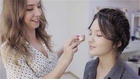 Artista de maquillaje del estilista que hace maquillaje y el pelo en un sal?n de belleza almacen de metraje de vídeo