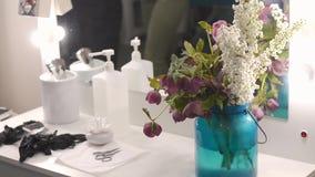 Artista de maquillaje del lugar de trabajo o browmaker Una tabla, un manojo de flores coloridas, pinzas, esponjas de algodón y lí almacen de video
