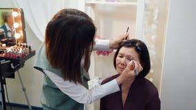 Artista de maquillaje Dying Eyebrows para la mujer mayor almacen de metraje de vídeo