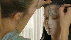 Artista de maquillaje en el trabajo que aplica el maquillaje de Halloween metrajes