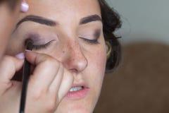 Artista de maquillaje de la boda que hace a una novia del compensar fotos de archivo
