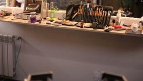 Artista de maquillaje profesional en la tabla en el estudio Lápiz labial multicolor, sombras, fundación del maquillaje profesiona almacen de metraje de vídeo