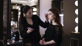 Artista de maquillaje profesional en proceso de trabajo - corrige las cejas con el cepillo y las sombras marrones de la frente Vi almacen de video