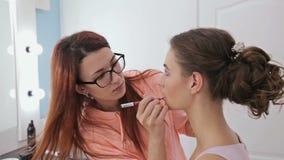Artista de maquillaje profesional que aplica contorno de los labios almacen de video