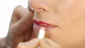 Artista de maquillaje profesional que aplica contorno en los labios del modelo cosméticos de la industria de moda almacen de video