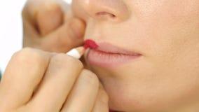 Artista de maquillaje profesional que aplica contorno en los labios del modelo cosméticos de la industria de moda metrajes
