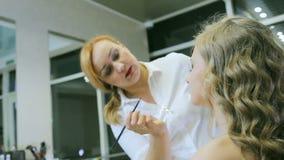 Artista de maquillaje profesional que aplica el lápiz y el cepillo del ojo al párpado rubio de los modelos para hacer flechas del almacen de metraje de vídeo