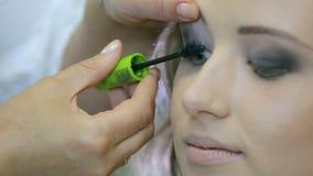 Artista de maquillaje profesional que aplica el rimel a las pestañas rubias de los modelos metrajes