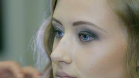 Artista de maquillaje profesional que aplica el rimel a las pestañas rubias de los modelos almacen de video