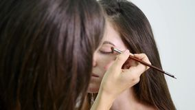 Artista de maquillaje profesional que aplica el sombreador de ojos al ojo modelo usando cepillo especial Maquillaje natural en sa metrajes