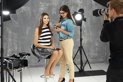 Artista de maquillaje profesional que trabaja con la mujer joven en el tiroteo de foto fotos de archivo libres de regalías