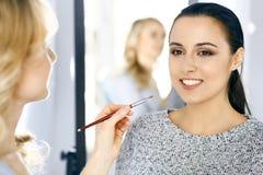Artista de maquillaje profesional que trabaja con la mujer joven hermosa Estilo nupcial, de la moda o del desnudo fotografía de archivo