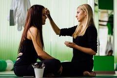 Artista de maquillaje profesional que trabaja con la mujer joven hermosa modelos de la aptitud, aero- yoga Siéntese en la posició Fotografía de archivo libre de regalías