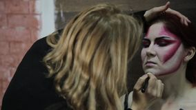 Artista de maquillaje que aplica maquillaje al modelo Muchacha modelo atractiva con el maquillaje de Halloween almacen de video