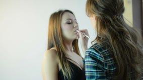 Artista de maquillaje que aplica contorno de los labios con el creyón especial metrajes