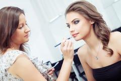 Artista de maquillaje que aplica el lápiz labial Foto de archivo