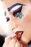 Artista de maquillaje que aplica el lápiz labial en los labios modelo con el cepillo foto de archivo libre de regalías