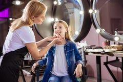 Artista de maquillaje que aplica el lápiz labial a los labios de su cliente Imagen de archivo