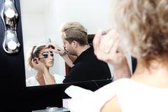 Artista de maquillaje que aplica el rimel en latigazos del ojo del modelo foto de archivo libre de regalías