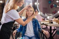 Artista de maquillaje que aplica el rimel a las pestañas de las muchachas Imagen de archivo libre de regalías