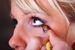 Artista de maquillaje que aplica el sombreador de ojos Foto de archivo libre de regalías