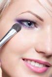 Artista de maquillaje que aplica el sombreador de ojos Imágenes de archivo libres de regalías