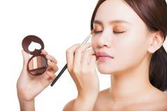 Artista de maquillaje que aplica el sombreador de ojos colorido en el ojo del modelo fotografía de archivo