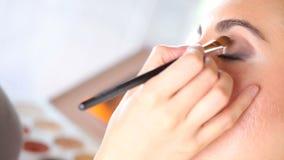 Artista de maquillaje que aplica el sombreador de ojos en el párpado usando cepillo almacen de video