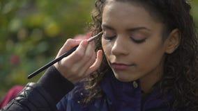 Artista de maquillaje que aplica el sombreador de ojos en ojos del modelo o de la actriz, blog de la belleza metrajes
