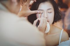 Artista de maquillaje que aplica el sombreador de ojos rosado al modelo asi?tico hermoso foto de archivo