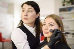 Artista de maquillaje que aplica el tono de la fundación usando cepillo especial en modelo hermoso joven de la cara Cuidado facia imagen de archivo