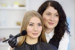 Artista de maquillaje que aplica el tono de la fundaci?n usando cepillo especial en modelo hermoso joven de la cara Cuidado facia imagen de archivo libre de regalías