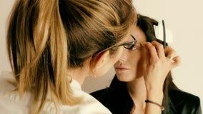 Artista de maquillaje que aplica maquillaje en la cara modelo del ` s almacen de metraje de vídeo