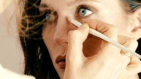 Artista de maquillaje que aplica maquillaje en la cara modelo del ` s almacen de video