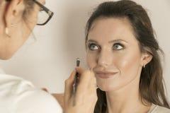 Artista de maquillaje que aplica maquillaje en la cara modelo del ` s foto de archivo