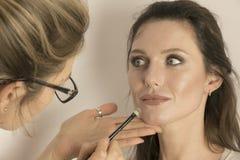Artista de maquillaje que aplica maquillaje en la cara modelo del ` s fotos de archivo libres de regalías