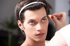 Artista de maquillaje que aplica la fundación con un cepillo, hombre en el espejo del vestuario foto de archivo libre de regalías