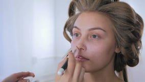 Artista de maquillaje que aplica la fundación tonal líquida en cara del ` s de la mujer metrajes