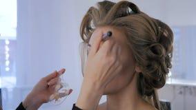 Artista de maquillaje que aplica la fundación tonal líquida en cara del ` s de la mujer almacen de metraje de vídeo