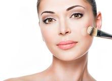 Artista de maquillaje que aplica la fundación tonal líquida en la cara Fotos de archivo libres de regalías