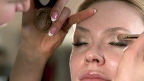 Artista de maquillaje que aplica maquillaje de la pestaña al ojo modelo rubio del ` s Ciérrese encima de la visión metrajes