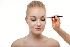 Artista de maquillaje que aplica la sombra de ojos para la mujer joven hermosa en el fondo blanco foto de archivo