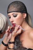Artista de maquillaje que aplica lustre del labio en la cara de la mujer Muchacha de la belleza con lustre y la redecilla del lab Foto de archivo libre de regalías