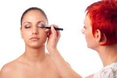 Artista de maquillaje que aplica maquillaje en la ceja Imagenes de archivo